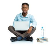 African american college student sitting with laptop on white ba Stock Photo