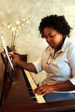 African American Composer. A young African American lady sits at the piano picking out a tune that she is composing Royalty Free Stock Image