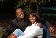 African-American couple. Smiling sitting in the grass Stock Photo