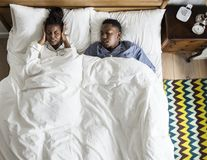 African American couple on bed, man snoring and disrupting woman. African American couple on bed, men snoring and disrupting woman`s sleep Royalty Free Stock Image