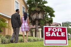 African American Couple Beside House For Sale Sign Stock Photo