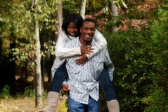 African-American couple bonding outside. African-American couple enjoying the outside fall weather, while the man carries his lady piggyback royalty free stock photography