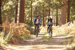 African American Couple Cycling Through Fall Woodland Royalty Free Stock Image