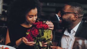 African American Couple Dating in Restaurant. Romantic Couple in Love Dating. Cutel Man and Girl in a Restaurant Making Order. Romantic Concept. Man Giving stock photos