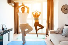 African American couple doing yoga exercises at home. They stand on the floor on yoga mats. A men and a women are doing leg exercises. They smile at each other royalty free stock photo