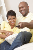 African American Couple Eating Popcorn With Remote. A happy African American men and women couple in their thirties sitting at home, eating popcorn using remote Stock Photography