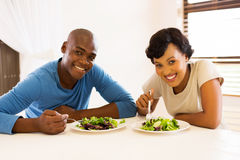 African american couple eating. Portrait of young african american couple eating healthy salad for lunch Stock Photo