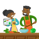 Couple looking for a recipe in a digital tablet. African-american couple following a vegetable meal recipe on tablet and cooking meal together. Couple looking Royalty Free Stock Photos