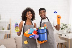 African-american couple holding cleaning tools and detergents. Happy african-american couple holding lots of detergents, ready for spring cleaning of apartment royalty free stock photos