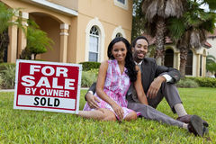 African American Couple & House For Sale Sold Sign. A happy African American man and woman couple outside a large house with a For Sale Sold sign royalty free stock image