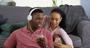 African American couple listen to music and browse internet with smartphones. African American couple listen to music and browse internet with their smartphones stock image