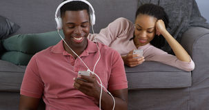 African American couple listening to music and using smartphone Royalty Free Stock Photo