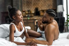 african american couple looking at each other on bed royalty free stock images