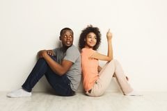 African-american couple looking up, sitting on floor. African-american family couple looking up, sitting on floor back to back in new apartment, dreaming about Stock Photography