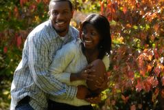 African-American couple play football. African-American couple together outside on a fall day bonding and riding piggy back royalty free stock photos