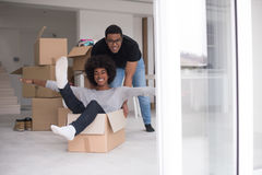 African American couple  playing with packing material. African American couple sitting in a box playing with packing material, having fun after moving in new Royalty Free Stock Photography