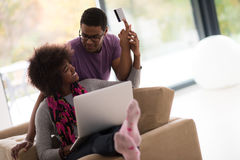 African american couple shopping online. Happy young african american couple shopping online through laptop using credit card at home Stock Photos