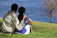 African American Couple Sitting By Lake. Rear view of African American man and woman couple sitting by a blue lake with a single tree. Concept shot for love Royalty Free Stock Photo