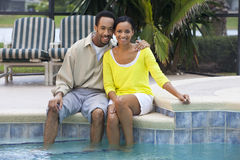 African American Couple Sitting By A Swimming Pool Royalty Free Stock Photos