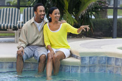 African American Couple Sitting By Swimming Pool. A happy African American man and woman couple in their thirties sitting outside by a pool smiling and pointing Royalty Free Stock Photo