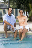 African American Couple By Swimming Pool. A happy African American man and woman couple in their thirties sitting with their feet in a swimming pool royalty free stock photo