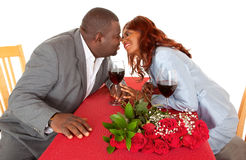 African American Couple About to Kiss in Romantic Dinner. An African American couple are touching hands and about to kiss in romantic dinner Stock Image