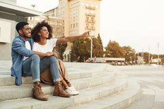 African-american couple of tourists walking in city, copy space. Look here. African-american couple of tourists walking in city, women pointing somewhere, copy royalty free stock image