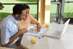 African American Couple Using Laptop Computer. A successful African American man and woman couple in their thirties using a laptop computer to look for property Stock Image