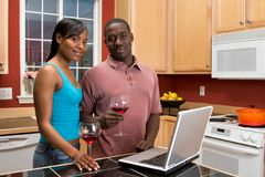 African American Couple Using Laptop in Kitchen Royalty Free Stock Photos