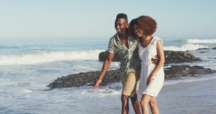 African American couple walking seaside and kissing