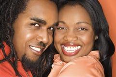 African-American couple wearing orange clothing. Smiling African-American mid-adult couple wearing orange clothing on orange background Stock Image