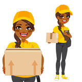African American Courier. Young woman courier delivering cardboard box parcel in yellow and black uniform Royalty Free Stock Photography