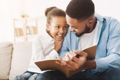 African-american dad and daughter spending time, reading book. African-american dad and daughter spending time together, reading book at home royalty free stock images