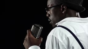 African American the darkness comes to the microphone singing in a recording studio. Black background. Slow motion stock video