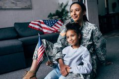 Daughter and soldier with american flag. African american daughter and female soldier in military uniform with american flag at home stock photography