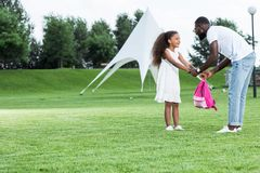 African american daughter giving school bag to father. In park stock photos