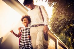 Funny talk about school. African American daughter and her father walking trough city park and talking royalty free stock photos