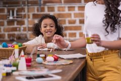 African american daughter looking how mother painting easter eggs Royalty Free Stock Photo