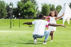 African american daughter with school bag running to father with open arms. In park stock photography