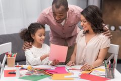 Daughter showing parents sketch of greeting card on mothers day. African american daughter showing parents sketch of greeting card on mothers day Royalty Free Stock Photography