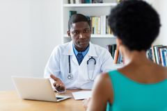 African american doctor explaining diagnosis to female patient. At hospital royalty free stock photography