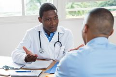 African american doctor explaining diagnosis to patient. African american doctor explaining diagnosis to sick patient at hospital stock images