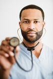 African American Doctor Holding Up A Stethoscope Stock Photo