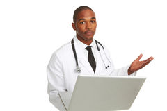 African-American doctor with laptop confused. Portrait of young African-American doctor holding laptop stumped in front of white background, studio shot Stock Images