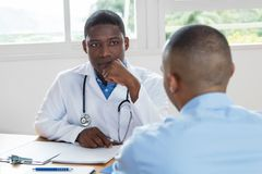 African american doctor listening to problems of patient. African american doctor listening to problems of sick patient at hospital Royalty Free Stock Photos