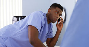 African American doctor on mobile talking to colleague and using computer Royalty Free Stock Photo