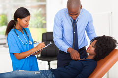 Doctor examining patient. African american doctor and nurse examining female patient on examining couch royalty free stock photos