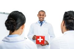 african american doctor presenting red first aid kit, stock photo