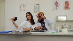 African American doctor and pretty nurse taking silly selfies on the phone stock footage