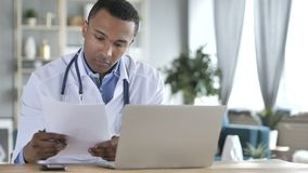 African-American Doctor Reading medical Report, Diagnosing Patient stock video footage